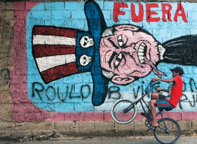 "A boy cycles past anti-U.S graffiti with the word ""out"" in Caracas"